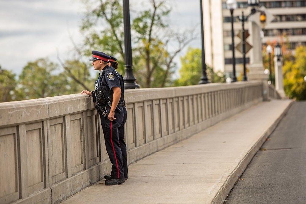 2 Peterborough Police Officers look over the side of a large concrete bridge