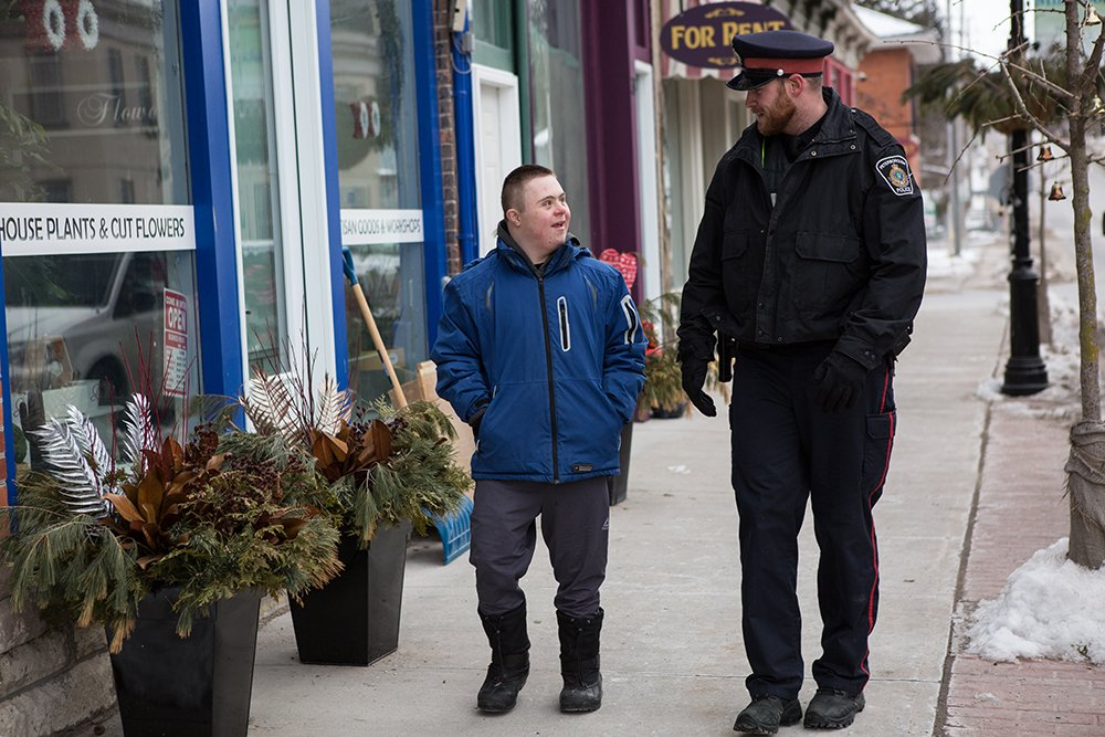 A Peterborough Police officer walks down the street with a citizen while having a lighthearted conversation
