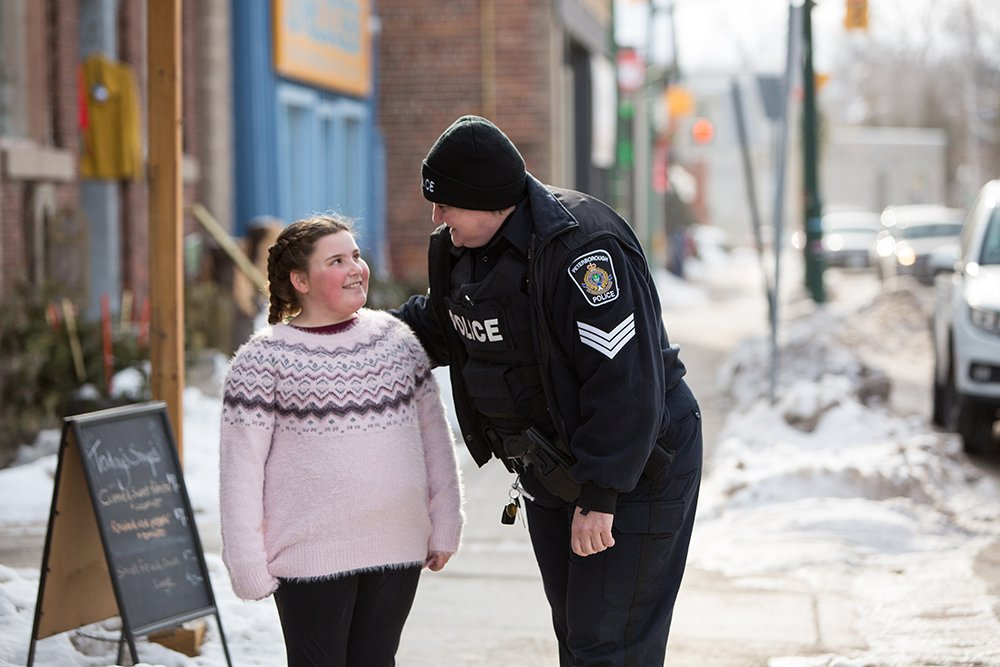 A Peterborough Police officer leans down to speak with a young girl on a winter street