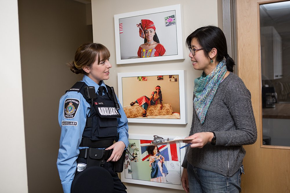 A police officer from the Auxiliary unit has a conversation with a woman in a hallway in front of portraits