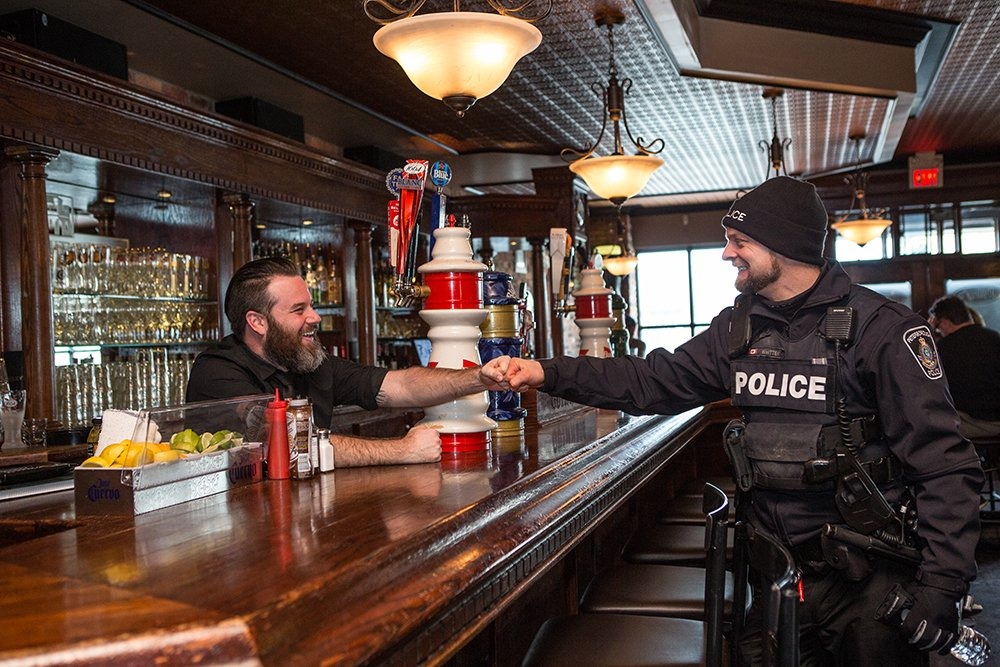 A Peterborough POlice officer fist bumps a bartender across the pub bar