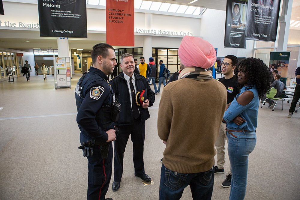 2 Peterborough Police officers engaged in casual conversation with citizens at Fleming College