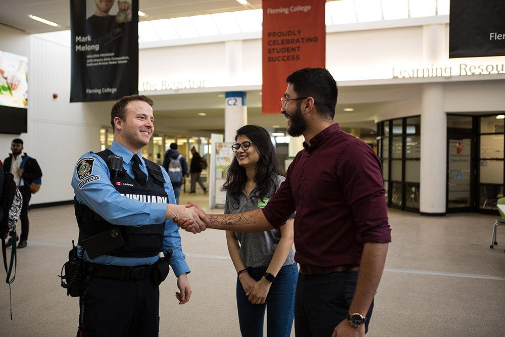 A police officer from the auxiliary unit shakes hands with a man at Fleming university in front a woman who is standing nearby
