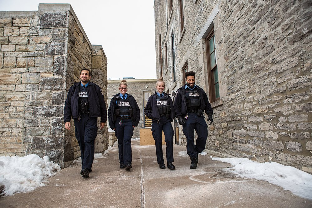 4 special constables walk laughing between 2 stone buildings