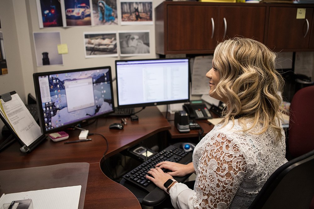 A city clerk sits behind a desk typing an email