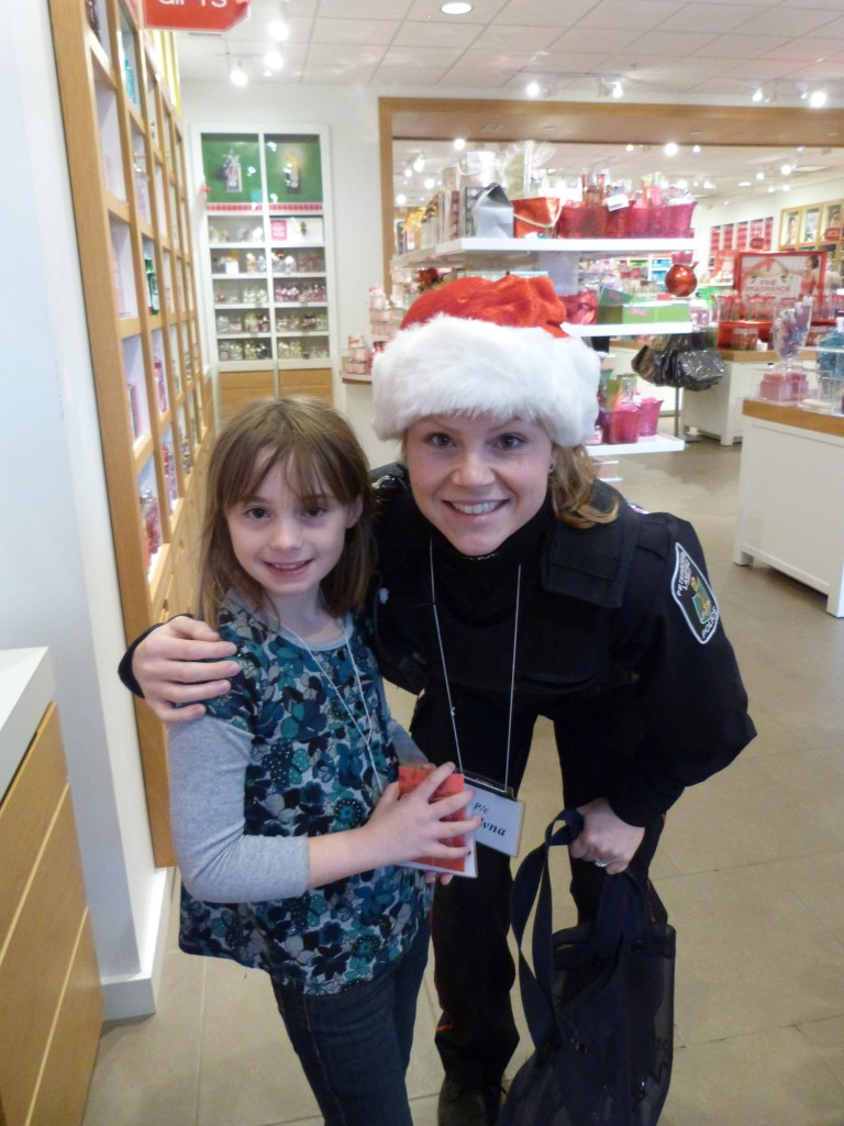A police officer wearing a santa hat stands with her arm around her child in a store