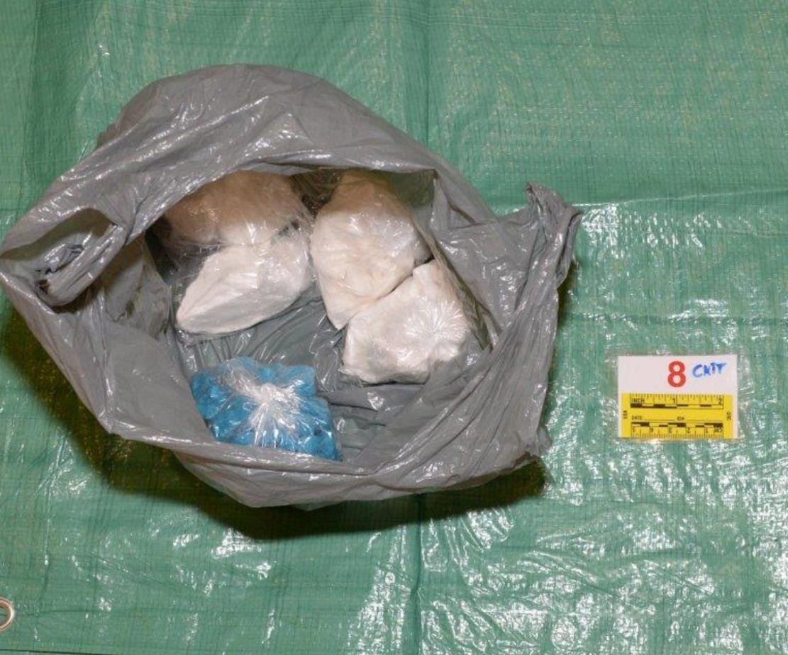 5 small bags of drugs  are pictures in a larger grey plastic shopping bag