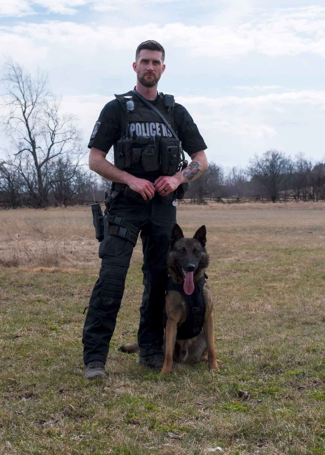 A police officer stands beside a seated dog from the K-9 Units
