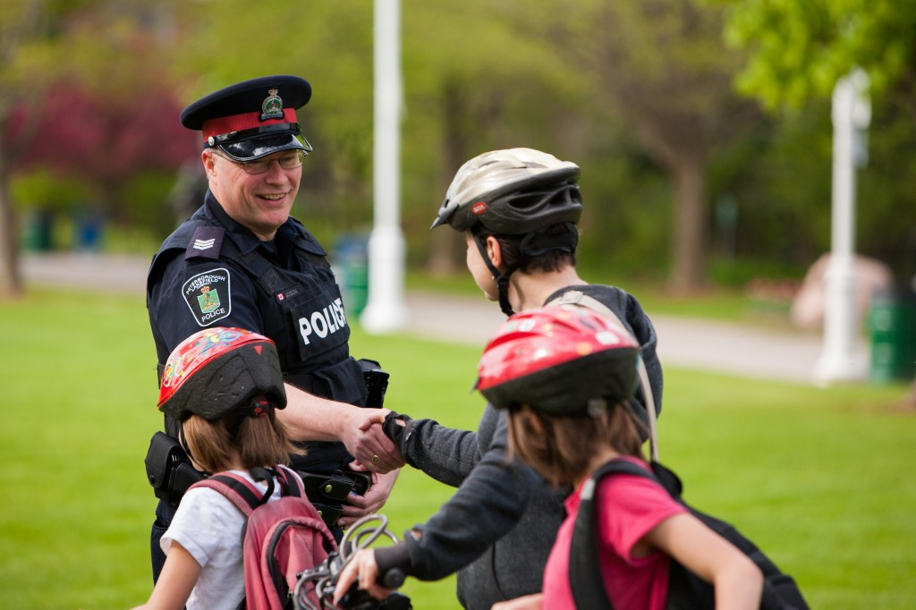 A police officer shakes hands with children who are wearing their bike helmets in a park
