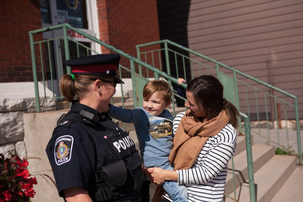 A Peterborough Police officer smiles at a small child that is being held by their mother while the child reaches out to the police officer